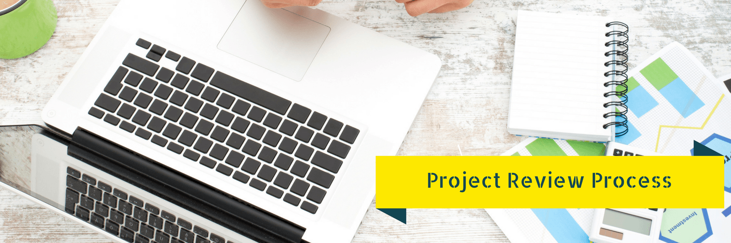 Image of a laptop, notebook and plans on the table - Graphic says Project Review Process