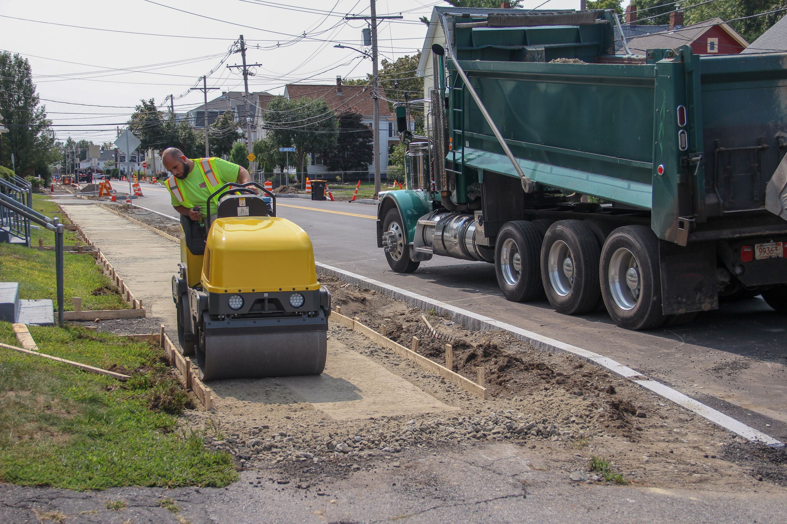 Image of a roller compacting base material in preparation of pouring sidewalks.